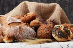 Assortment of baked bread and bread rolls on wooden table background